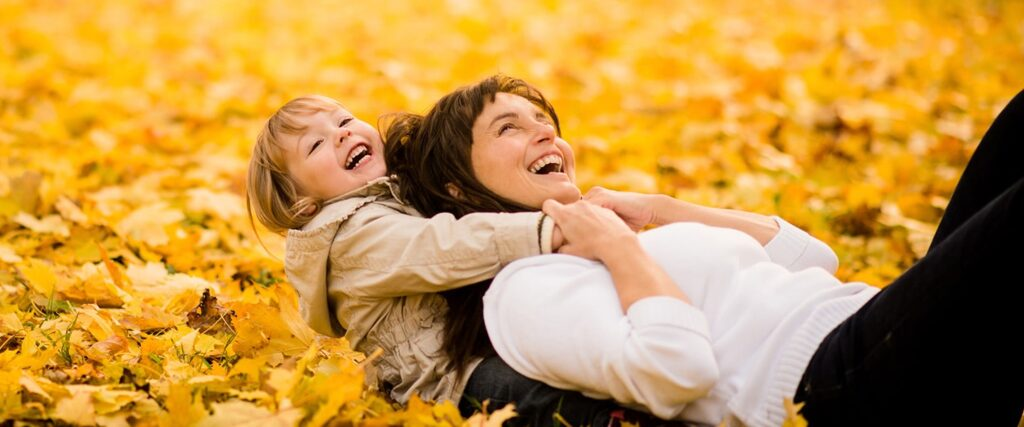 mother daughter playing august fall leaves yellow happy